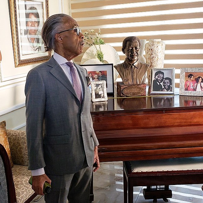Rev. Sharpton stands in Nelson Mandela's last residence in Johannesburg next to piano with photographs and a bust of Mandela.